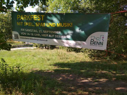 Banner auf einer Wiese mit Ankündigung zum Fest
